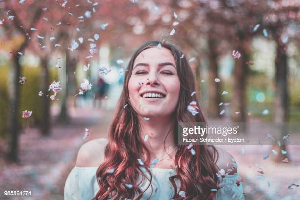 petals falling on smiling young woman against trees - blütenblatt stock-fotos und bilder