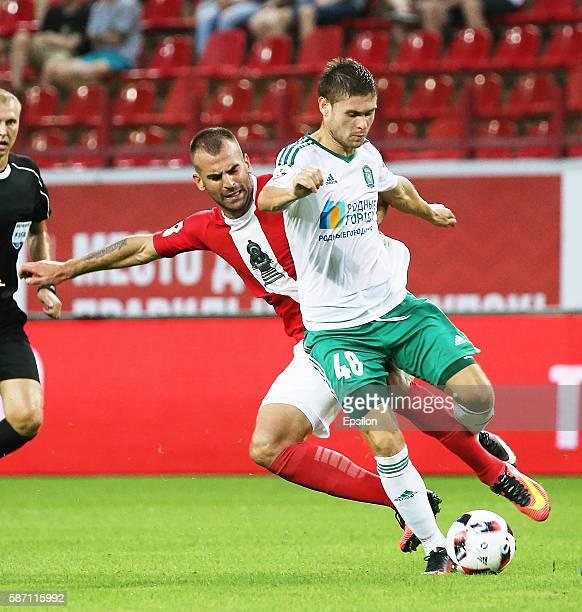 Petar Skuletic of FC Lokomotiv Moscow challenged by Maksim Tishkin of FC Tom Tomsk during the Russian Premier League match between FC Lokomotiv...
