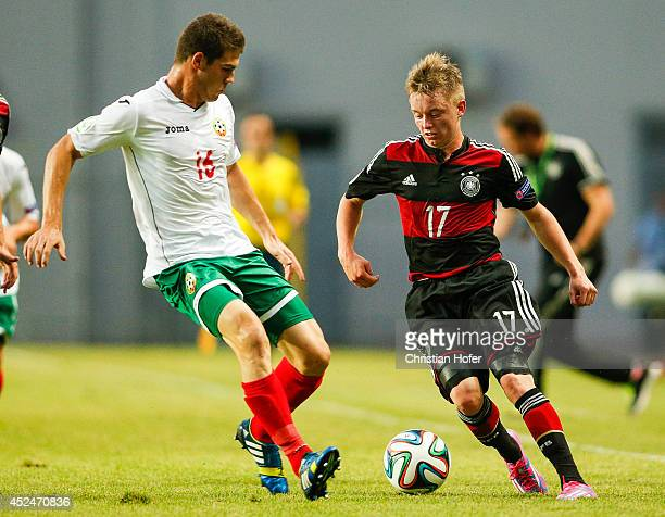 Petar Vitanov of Bulgaria competes for the ball with Benjamin Truemmer of Germany during the UEFA Under19 European Championship match between U19...