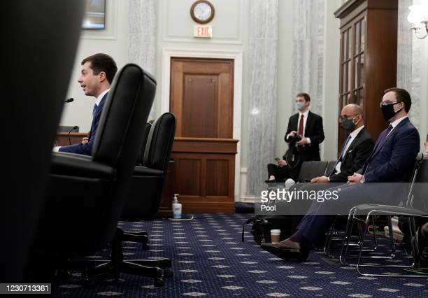 Pete Buttigieg speaks as his husband Chasten Buttigieg looks on during a Senate Commerce, Science, and Transportation committee hearing to examine...