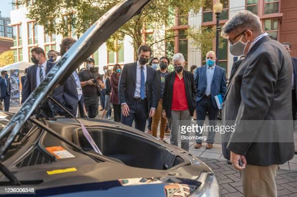 Pete Buttigieg, U.S. Secretary of transportation, center left, and Gina McCarthy, White House national climate advisor, center right, examine a Tesla...