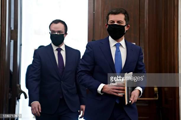 Pete Buttigieg, U.S. Secretary of transportation nominee for U.S. President Joe Biden, right, wears a protective mask while arriving to a Senate...