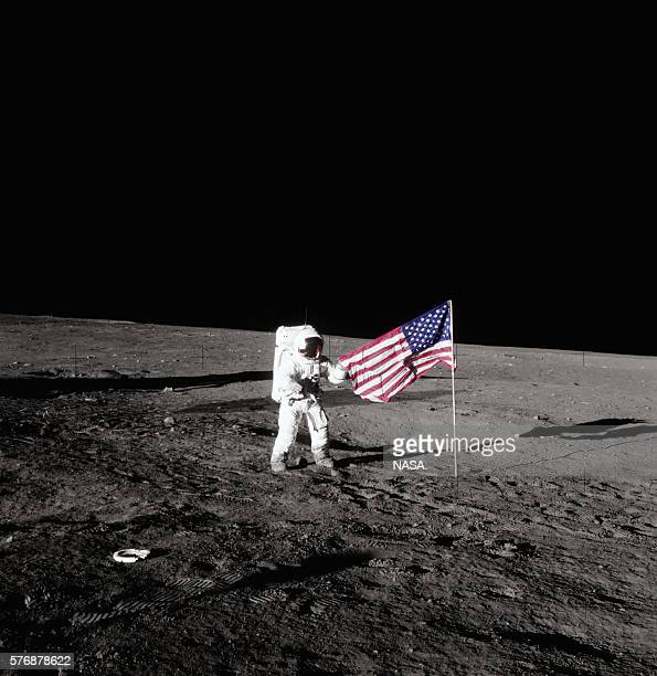 Pete Conrad of the Apollo 12 mission holds an American flag on the surface of the Moon
