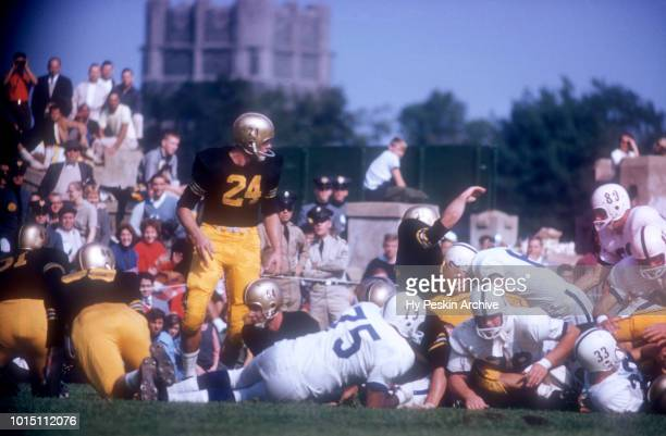 Pete Dawkins of the Army Cadets looks on as his teammate Bob Anderson is tackled by John Bozick of the Penn State Nittany Lions during an NCAA game...