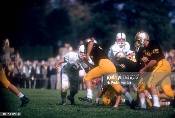 Pete Dawkins of the Army Cadets runs the fake as his teammate Harry Walters blocks Bill Wehmer of the Penn State Nittany Lions during an NCAA game on...