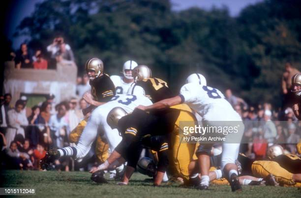 Pete Dawkins of the Army Cadets runs with the ball as Steve Garban of the Penn State Nittany Lions goes for the tackle during an NCAA game on October...
