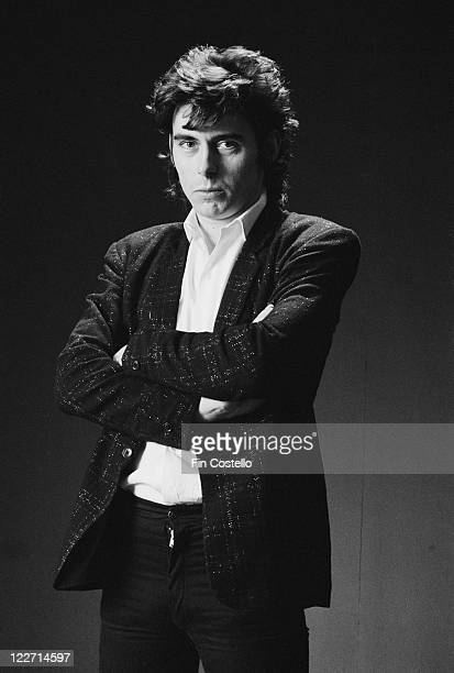 Pete Farndon , bassist with British rock band, The Pretenders, wearing a black jacket and a white shirt, with his arms folded, as he poses for a...