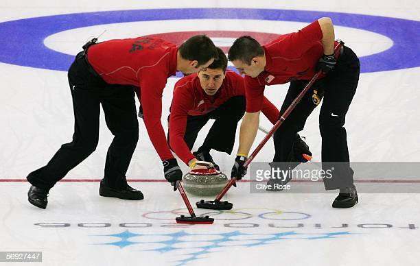 Pete Fenson of United States releases the stone as Shawn Rojeski and Joe Polo of United States brush the ice during the Gold medal match of the men's...