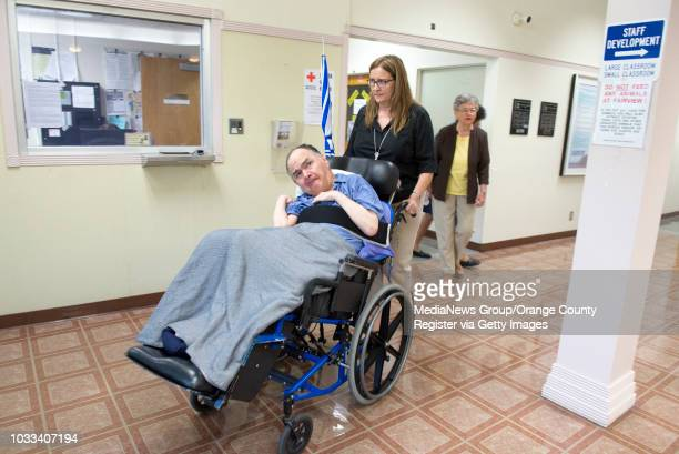 Pete Flavia left who has been a resident of Fairview Developmental Center since the 1980's is wheeled outside by Program Assistant Margo McLaughlin...