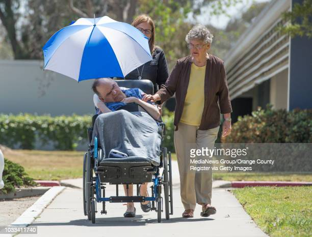 Pete Flavia left who has been a resident of Fairview Developmental Center since the 1980's is taken for a walk by Program Assistant Margo McLaughlin...