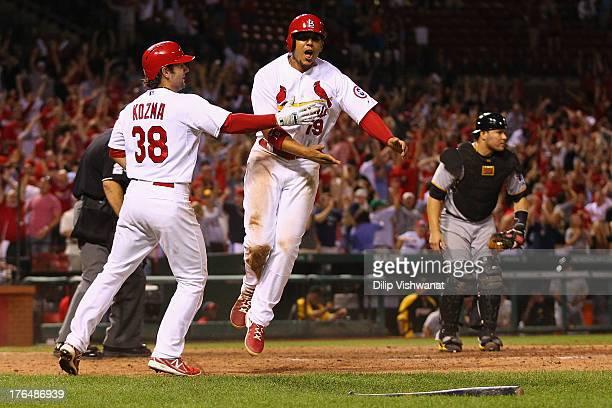 Pete Kozma and Jon Jay both of the St Louis Cardinals celebrate after Jay scores the gamewinning run against the Pittsburgh Pirates in the 14th...
