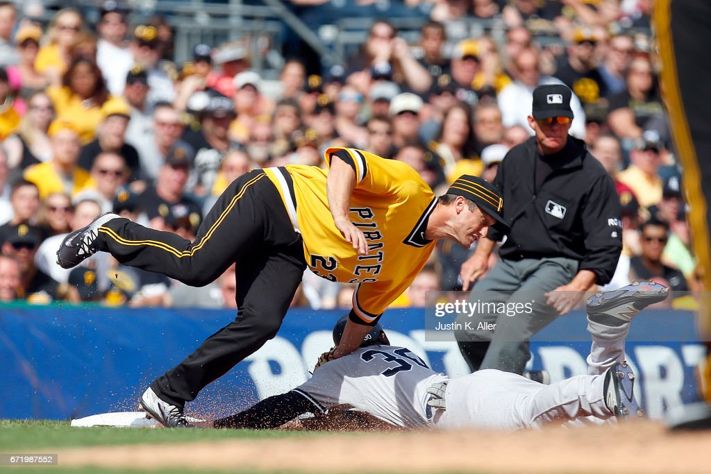 Pete Kozma #30 of the New York Yankees advances to third on a wild pitch against David Freese #23 of the Pittsburgh Pirates in the eighth inning at PNC Park on April 23, 2017 in Pittsburgh, Pennsylvania.