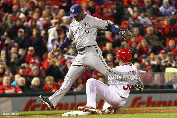 Pete Kozma of the St Louis Cardinals beats Jean Segura of the Milwaukee Brewers to third base on a bunt by Shelby Miller of the Cardinals at Busch...