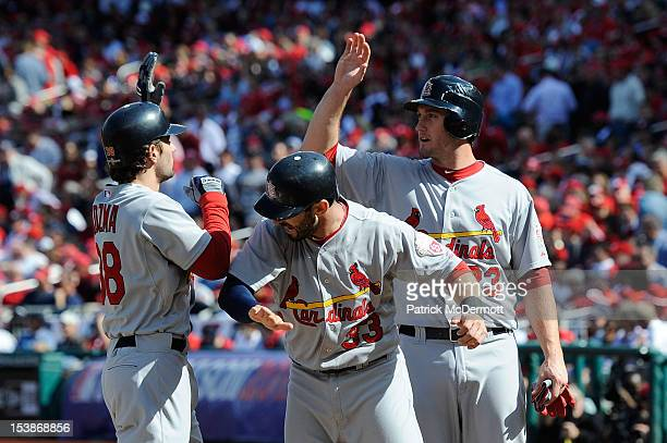 Pete Kozma of the St Louis Cardinals celebrates with teammates Daniel Descalso and David Freese after hitting a three run home run in the second...
