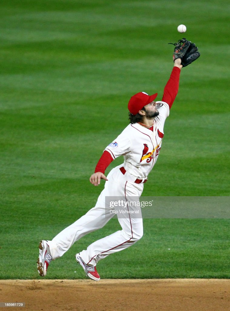 Pete Kozma #38 of the St. Louis Cardinals fails to catch a ball hit by Xander Bogaerts #72 of the Boston Red Sox in the eighth inning of Game Three of the 2013 World Series at Busch Stadium on October 26, 2013 in St Louis, Missouri.