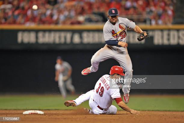 Pete Kozma of the St Louis Cardinals leaps to avoid the slide of Devin Mesoraco of the Cincinnati Reds as he throws to first base to complete a...