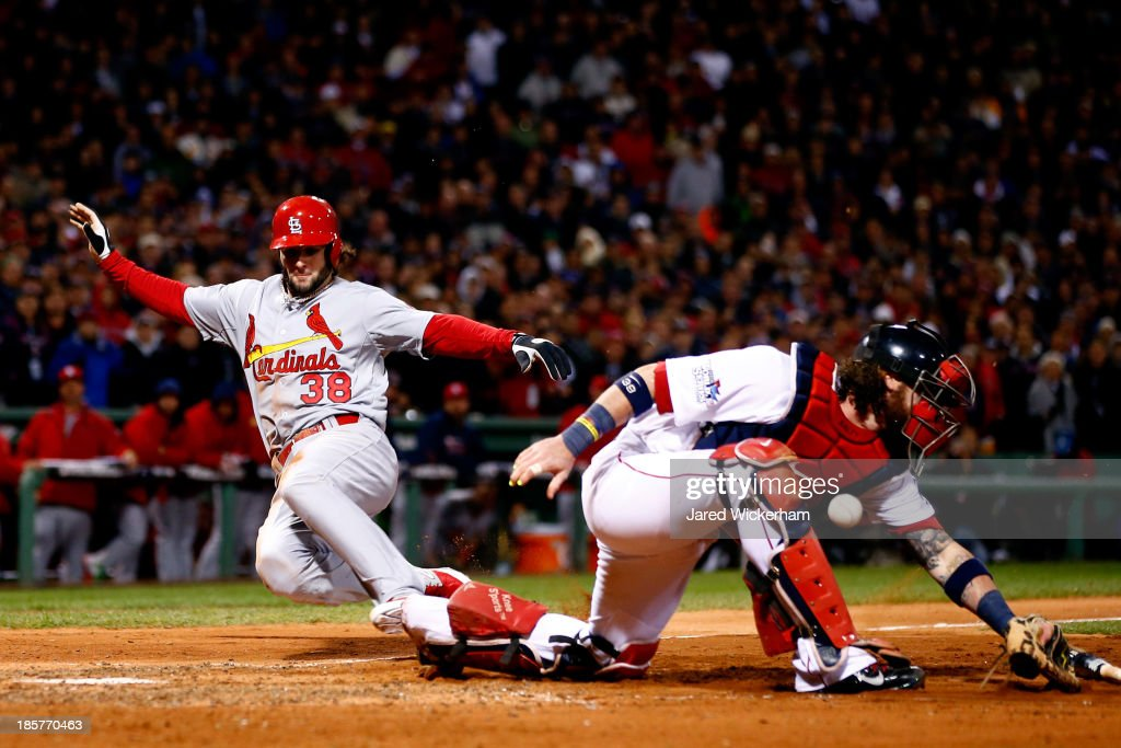 Pete Kozma #38 of the St. Louis Cardinals scores in the seventh inning as Jarrod Saltalamacchia #39 of the Boston Red Sox loses the ball during Game Two of the 2013 World Series at Fenway Park on October 24, 2013 in Boston, Massachusetts.