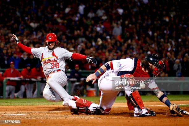 Pete Kozma of the St Louis Cardinals scores in the seventh inning as Jarrod Saltalamacchia of the Boston Red Sox loses the ball during Game Two of...