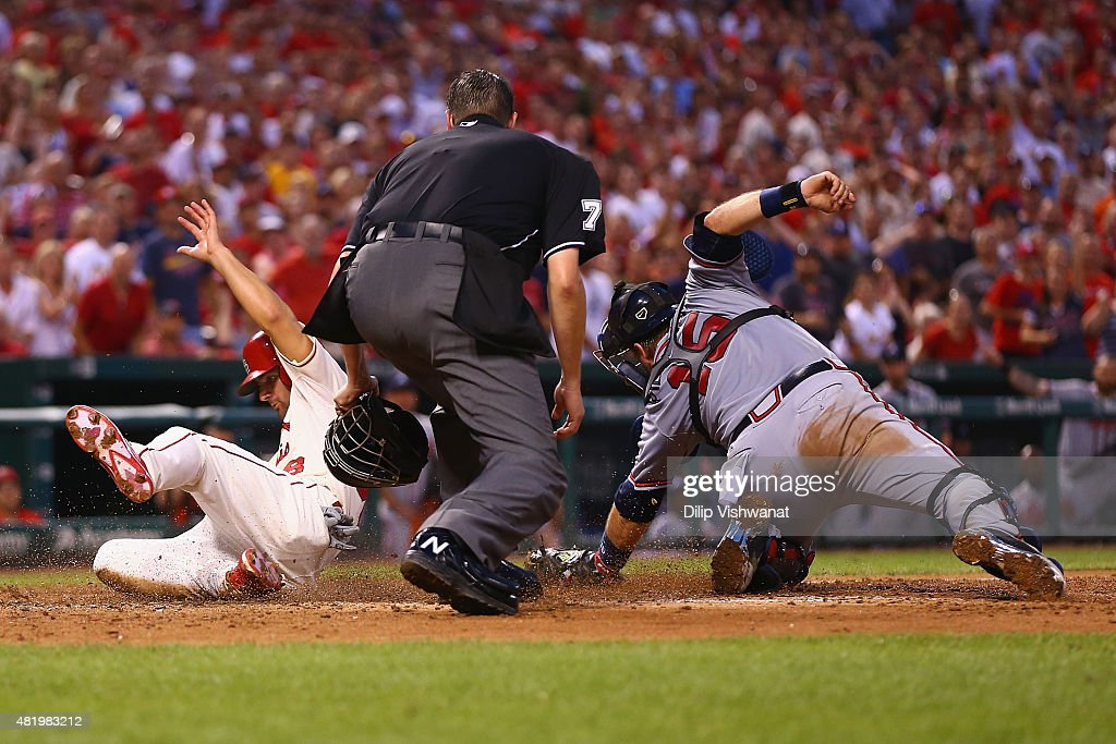 Pete Kozma #38 of the St. Louis Cardinals scores the game-winning run against A.J. Pierzynski #15 of the Atlanta Braves in the eighth inning at Busch Stadium on July 25, 2015 in St. Louis, Missouri.