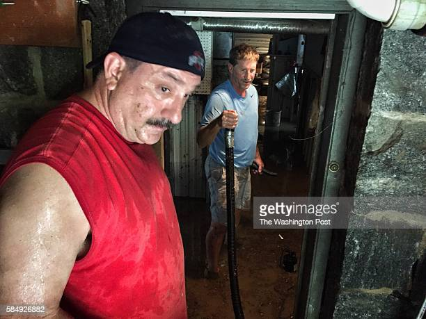 Pete Price left and Al Miller help neighbors drain a flooded basement in historic Ellicott City on Sunday July 31 in Ellicott City Marland Heavy...