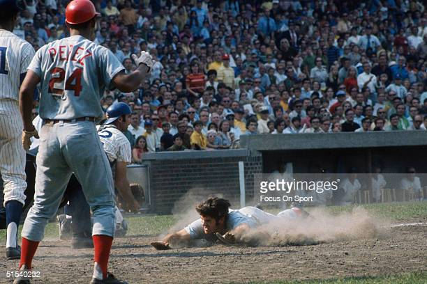 Pete Rose of the Cincinnati Reds beats the throw with a head first dive into home plate during a game against the Chicago Cubs at Wrigley Field...