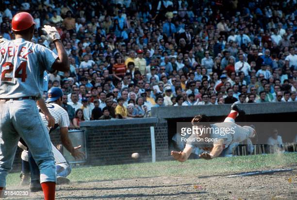 Pete Rose of the Cincinnati Reds dives head first into home plate during a game against the Chicago Cubs at Wrigley Field during the early 1970s in...