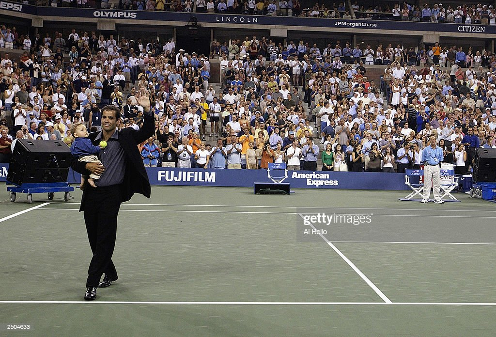 Pete Sampras circles the court with his son Christian at a ceremony to honor his retirement during the US Open on August 25, 2003 at the USTA National Tennis Center, Flushing Meadows Corona Park, in Flushing, New York.