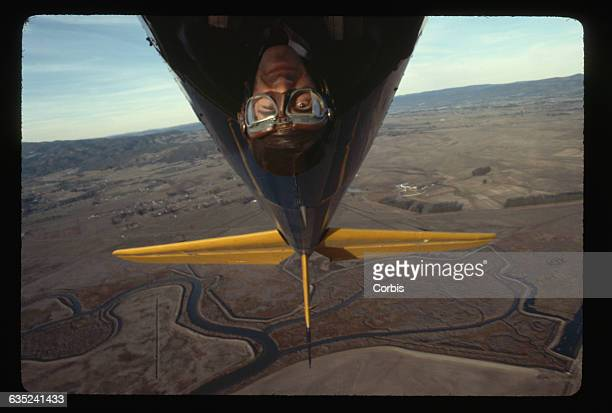 Pete Sears a member of Jefferson Starship flies his biplane upside down over farms and hills