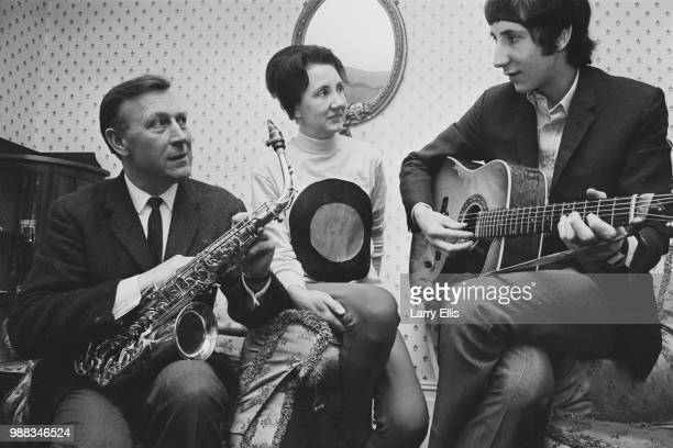 Pete Townshend of The Who pictured playing an acoustic guitar with his father Cliff Townshend , saxophone player with the Squadronaires, and mother...