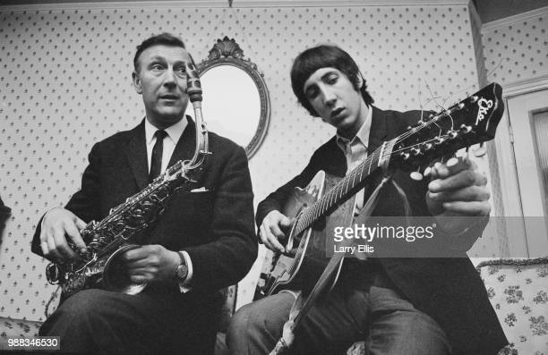 Pete Townshend of The Who pictured playing an acoustic guitar with his father Cliff Townshend saxophone player with the Squadronaires at home in...