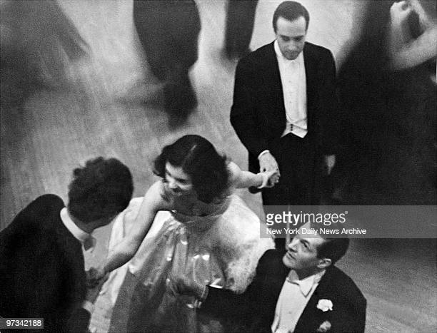 Peter Arno bottom right and to other admirers vie for a dance with Brenda Frazier at her debut