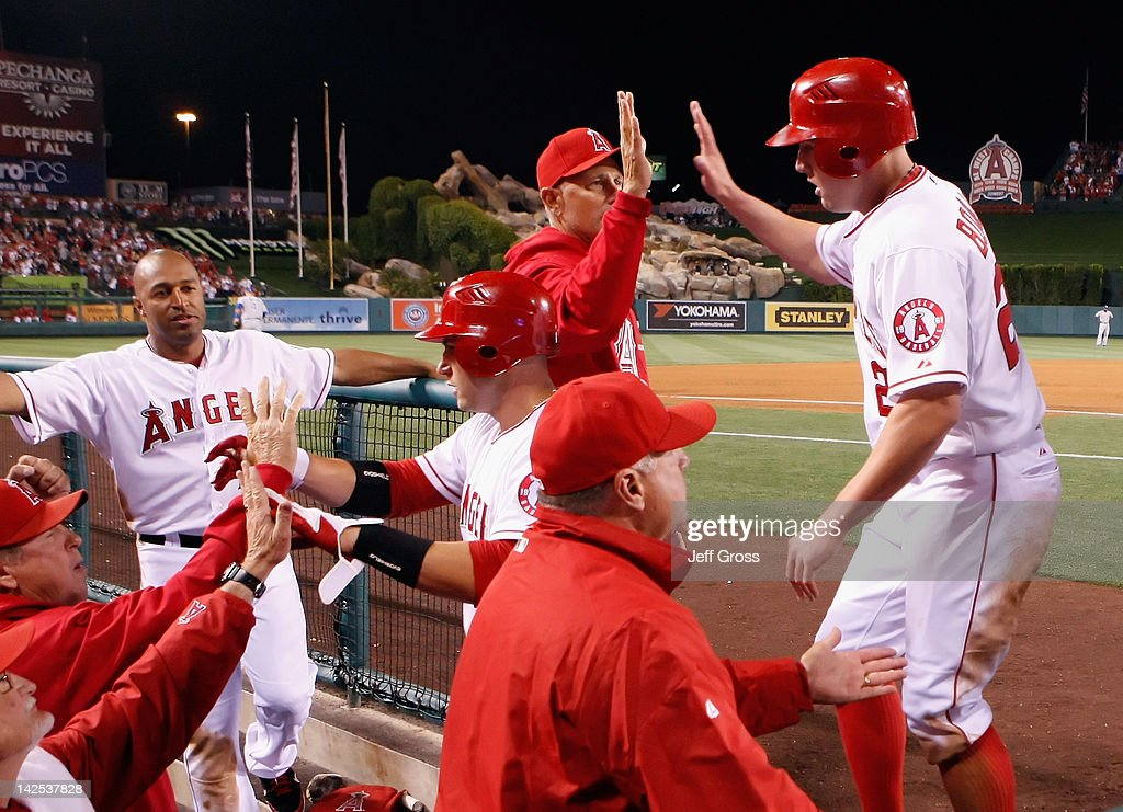 Peter Bourjos (R) #25 of the Los Angeles Angels of Anaheim receives high fives in the dugout after scoring on a triple by Erick Aybar (not pictured) in the eighth inning against the Kansas City Royals during the opening day game at Angel Stadium of Anaheim on April 6, 2012 in Anaheim, California. The Angels defeated the Royals 5-0.