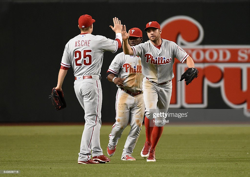 Peter Bourjos #17, Cody Asche #25 and Odubel Herrera #37 of the Philadelphia Phillies celebrate a 4-3 win against the Arizona Diamondbacks at Chase Field on June 28, 2016 in Phoenix, Arizona.