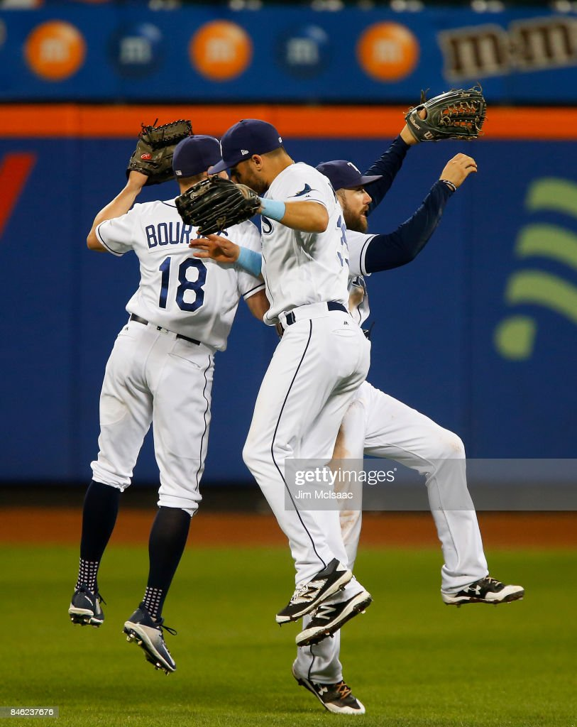Peter Bourjos #18, Kevin Kiermaier #39 (C) and Steven Souza Jr. #20 of the Tampa Bay Rays celebrate after defeating the New York Yankees at Citi Field on September 12, 2017 in the Flushing neighborhood of the Queens borough of New York City. The two teams were scheduled to play in St. Petersburg, Florida but due to the weather emergency caused by Hurricane Irma, the game was moved to New York, but with Tampa Bay remaining the 'home' team.