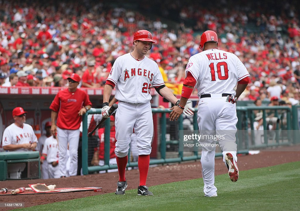 Peter Bourjos #25 of the Los Angeles Angels of Anaheim congratulates teammate Vernon Wells #10 after Wells scored in the fourth during the MLB game against the Baltimore Orioles at Angel Stadium of Anaheim on April 22, 2012 in Anaheim, California. The Orioles defeated the Angels 3-2 in ten innings.