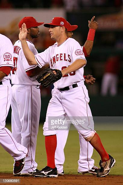 Peter Bourjos of the Los Angeles Angels of Anaheim highfives teammates after the victory against the Minnesota Twins at Angel Stadium on August 04...
