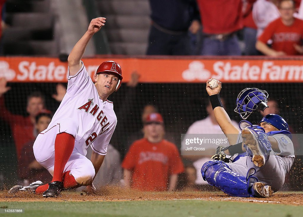 Peter Bourjos #25 of the Los Angeles Angels of Anaheim slides safely past the the tag of catcher Brayan Pena #27 of the Kansas City Royals on a triple by Erick Aybar (not pictured) in the eighth inning during the opening day game at Angel Stadium of Anaheim on April 6, 2012 in Anaheim, California. The Angels defeated the Royals 5-0.