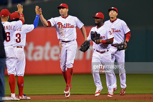 Peter Bourjos of the Philadelphia Phillies leads outfielders Odubel Herrera and Tyler Goeddel off the field while celebrating with Freddy Galvis and...