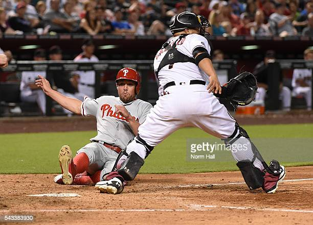 Peter Bourjos of the Philadelphia Phillies scores on a single by teammate Maikel Franco during the seventh inning as Welington Castillo of the...