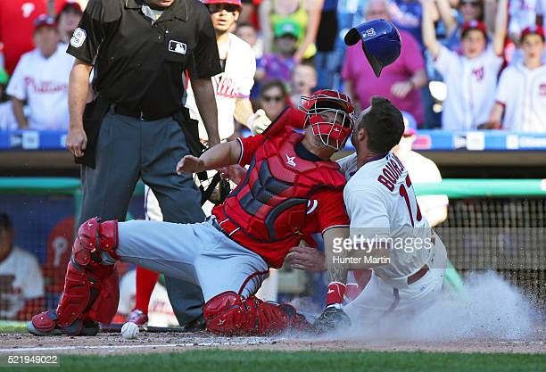 Peter Bourjos of the Philadelphia Phillies scores the game tying run as he collides with Jose Lobaton of the Washington Nationals in the tenth inning...