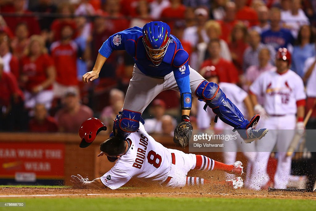 Peter Bourjos #8 of the St. Louis Cardinals scores the game-winning run against Miguel Montero #47 of the Chicago Cubs on a throwing error in the tenth inning at Busch Stadium on June 26, 2015 in St. Louis, Missouri. The Cardinals beat the Cubs 3-2 in 10 innings.