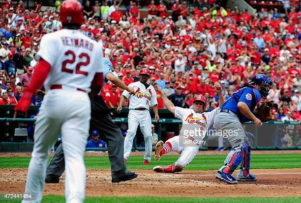 Peter Bourjos of the St Louis Cardinals slides safely past Miguel Montero of the Chicago Cubs as third base coach Jose Oquendo and Jason Heyward look...