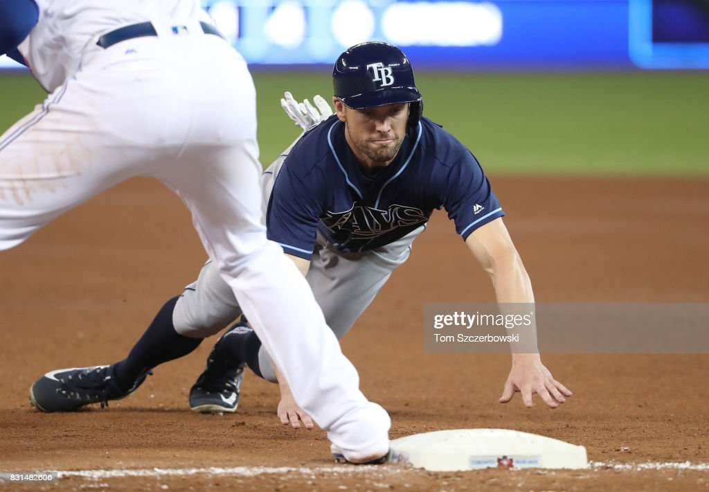 Peter Bourjos #18 of the Tampa Bay Rays dives back to first base safely on a pick-off attempt in the seventh inning during MLB game action against the Toronto Blue Jays at Rogers Centre on August 14, 2017 in Toronto, Canada.