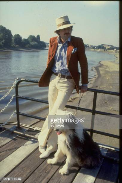 Peter Bowles, actor, by a river with his old english sheepdog, wearing a trilby, looking dandy. TVT Archive 1979 712.