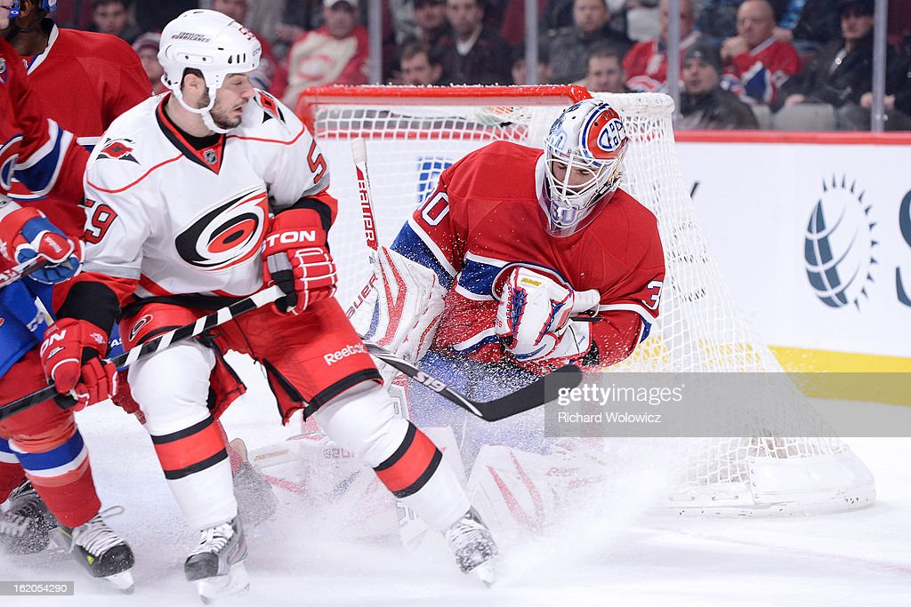 Peter Budaj #30 of the Montreal Canadiens stops the puck in front of Chad LaRose #59 of the Carolina Hurricanes during the NHL game at the Bell Centre on February 18, 2013 in Montreal, Quebec, Canada. The Canadiens defeated the Hurricanes 3-0.