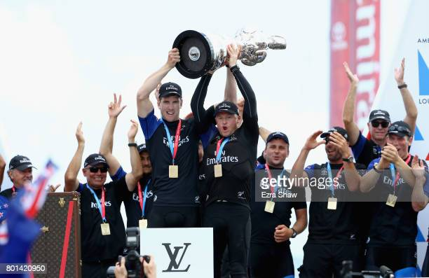 Peter Burling and Glenn Ashby of Emirates Team New Zealand lift the America's Cup trophy after they beat ORACLE TEAM USA on June 26, 2017 in...