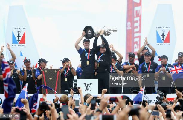Peter Burling and Glenn Ashby of Emirates Team New Zealand lift the America's Cup trophy after they beat ORACLE TEAM USA on June 26 2017 in Hamilton...