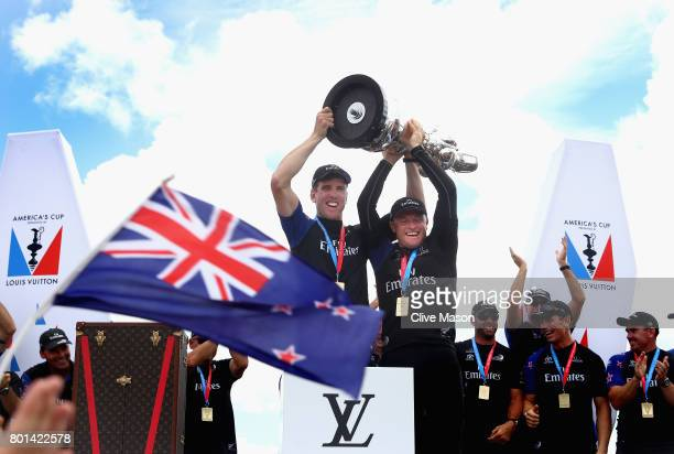 Peter Burling and Glenn Ashby of Emirates Team New Zealandlift the trophy after winning race 9 against Oracle Team USA to win the America's Cup on...