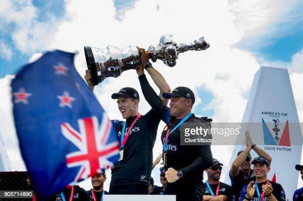 Peter Burling Helmsman and Glenn Ashby skipper of Emirates Team New Zealand lift the America's Cup trophy as Emirates Team New Zealand win race 9...