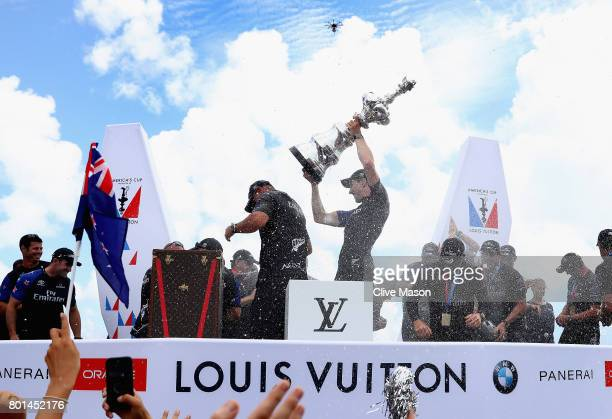 Peter Burling helmsman of Emirates Team New Zealand lifts the trophy after winning race 9 against Oracle Team USA to win the America's Cup on day 5...